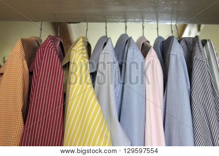 Colorful men's shirts hanging in wardrobe. Set of men's shirts on hangers. Ironed shirts hanging inside the closet.