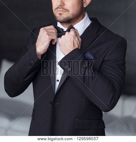 Sexy man dressing tuxedo and suit in luxury flat closeup