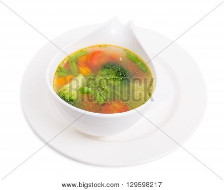 Bowl of minestrone soup with pesto. Isolated on a white background.