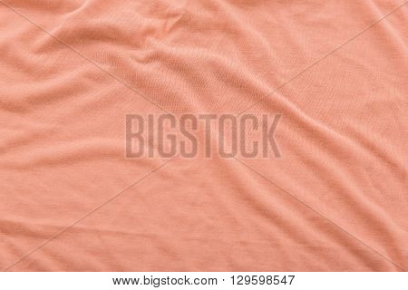 Close up of beautiful wrinkle coral color bedsheet fabric texture.