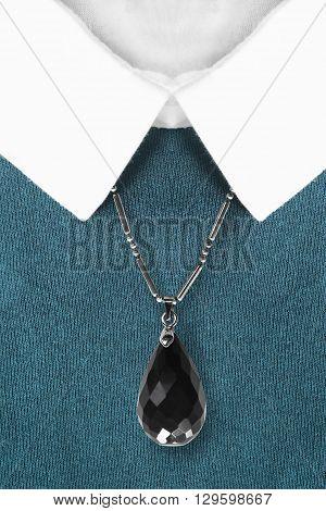 Black onyx pendant on blue pullover with white collar closeup