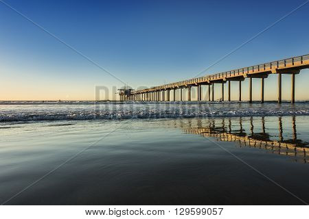 Wide angle shot of Scripps Pier with reflection during sunset in La Jolla, San Diego, California