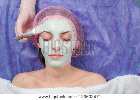 Closeup Young beautiful woman with clay facial mask at beauty salon. peeling in spa salon. Portrait of Young Woman having facial mask at beauty salon. Cosmetologist applying facial mask by brush
