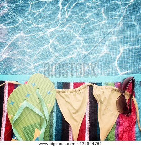 sandals ans swimming suit on towel border by poolside, retro toned