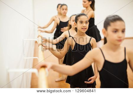 Cute Hispanic girls paying attention to class in a dance academy