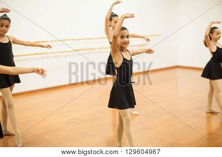 Portrait of a cute girl in leotard and skirt participating in a dance class and smiling