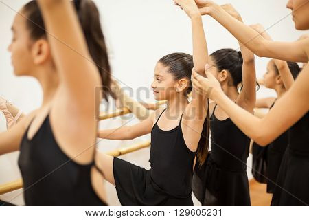 Portrait of a pretty girl with her leg up in a barre and getting help with her posture from her dance teacher