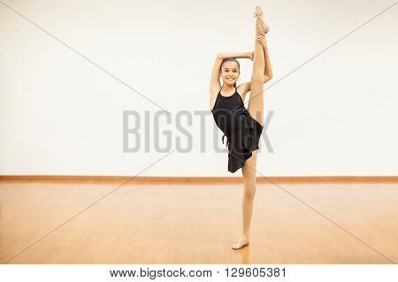 Full length portrait of a pretty girl in a leotard lifting her leg and doing a split in a dance studio and smiling