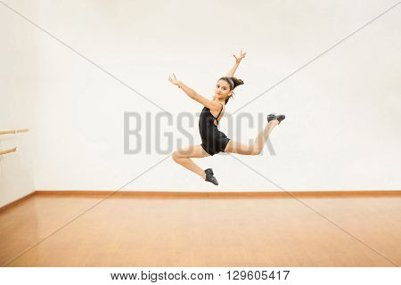 Cute girl jumping and holding a pose in the air in a dance studio
