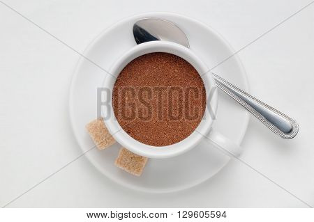 Coffee cup full of ground coffee on saucer with spoon and cane sugar cubes against white background, top view with space for text
