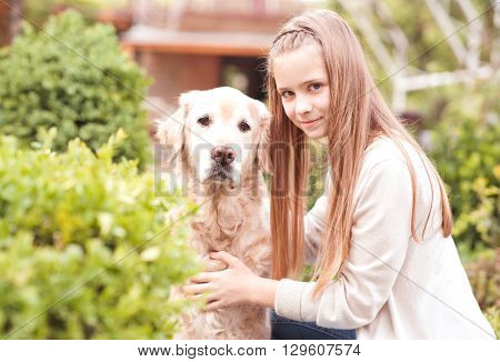 Smiling teen girl 12-14 year old holding beige labrador outdoors. Looking at camera. Happiness. Friendship.