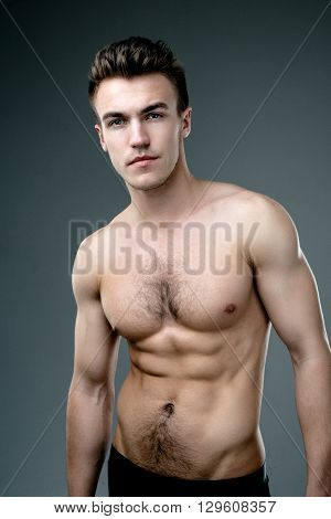 Young fashion topless man isolated on dark background