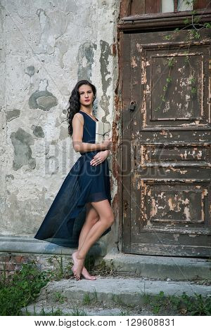 Young beautiful girl in vintage romantic antique dress with book near the vintage wooden door. fairy tale legend