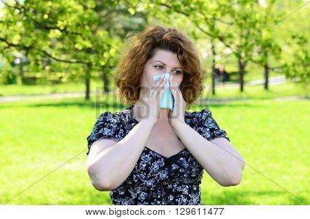 Woman closes nose with a tissue in the park, pollinosis