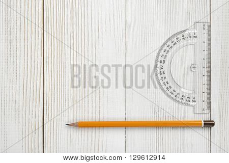 Layout with protractor and pencil on wooden surface. Top view composition. Measuring process. Work place of draftsman, architect, constructor. Engineering work. Construction and architecture. Working stuff.