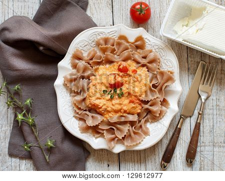 Wholegrain Pasta with stracchino cheese and fresh tomatoes top view