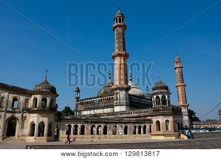 LUCKNOW, INDIA - DEC 19, 2012: Tourists walking around Asfi mosque of Bara Imambara complex at the sunny day on December 19, 2012 in Lucknow, India. Bara Imambara was built by Nawab of Lucknow in 1784.