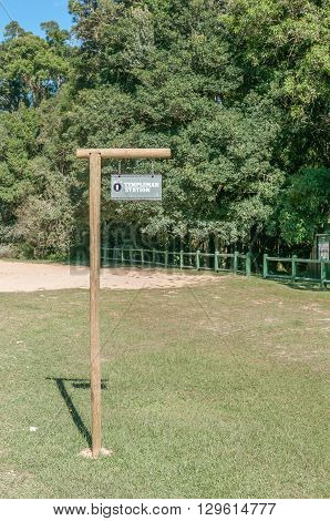KNYSNA SOUTH AFRICA - MARCH 5 2016: Signpost where the historic Templeman Station stood at the Ysterhoutrug picnic spot in the Knysna Forest. The railway ceased operation in 1949