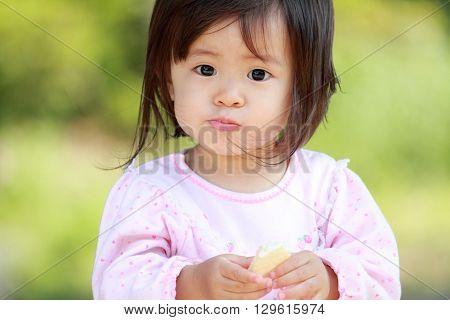 Japanese girl eating rice cracker (1 year old)