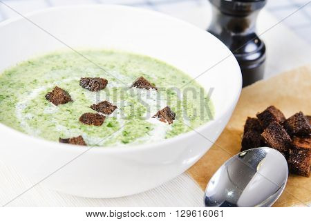 Spinach soup with croutons in white bowl. stock image.