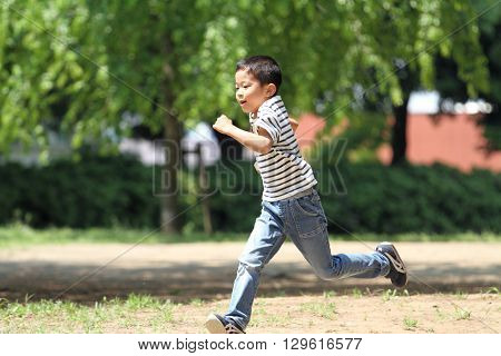Japanese boy running on the grass (first grade at elementary school)