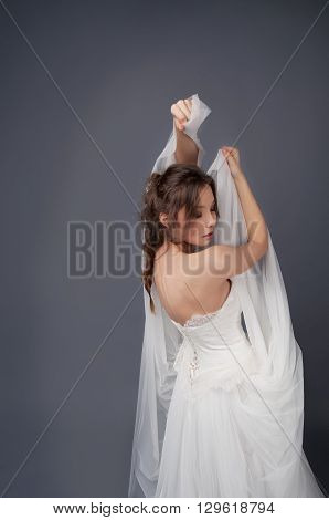 Bride in white wedding gown and beaded headpiece posing with veil