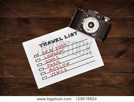 Vintage camera and drawing travel list on white paper