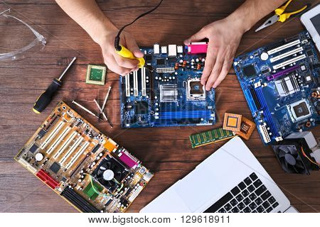 Male hands soldering motherboard on wooden table, top view