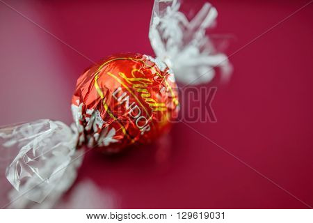 KILCHBERG SWITZERLAND - MARCH 20 2014: Tasty Lindt Lindor chocolate truffle on a red luxury silk background. Lindt is one one of the lastgest luxury chocolate and confectionery company worldwide with more than 30 factories worldwide