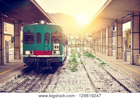Arrival of the local train to Trapani railway station at sunset. Sicily. Italy.
