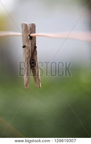 Closeup of woodenl clothes peg on a rope isolated on colored blurred background