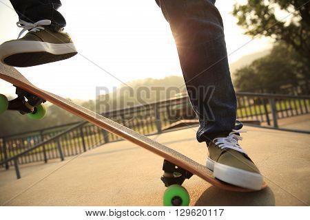 young skateboarder legs skateboarding at skatepark ramp