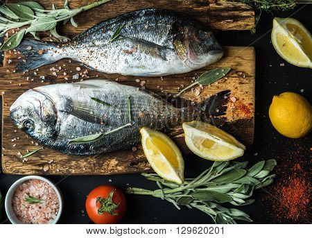 Fresh uncooked dorado or sea bream fish with lemon, herbs, oil, vegetables and spices on rustic wooden board over black backdrop, top view, horizontal