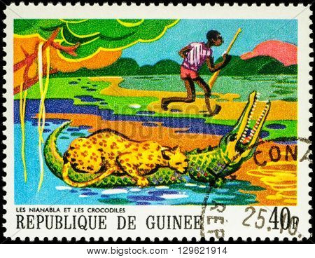 MOSCOW RUSSIA - MAY 12 2016: A stamp printed in Guinea shows leopard on a crocodile and a black hunter series
