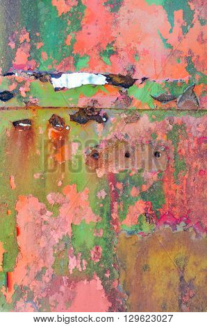 Old flaking paint, in multiple colors, on a rusting metal surface