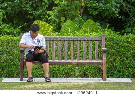 Labuan,Malaysia-April 3,2016:Asean man relaxing and enjoying his smart phone at Labuan garden on 3rd April 2016. Smartphone mobile apps concept.