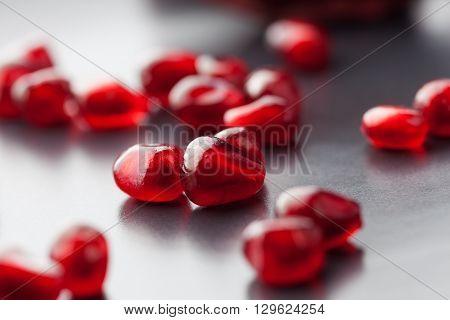 Pomegranate Seeds On Black Plate Extreme Closeup