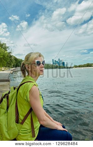 woman sitting in city park near Moscow river background is business Centre moscow-city