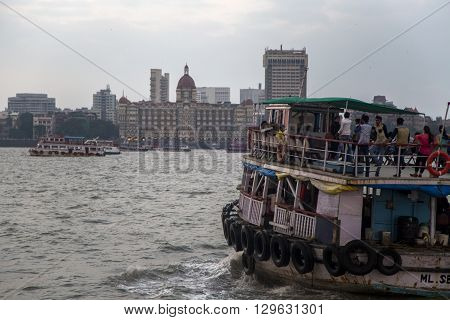 MUMBAI, INDIA - OCTOBER 11, 2015: Boat in front of the Taj Mahal Palace Hotel. This 5 star hotel is considered the flagship property of the group and contains 560 rooms and 44 suites. There are around 1500 staff including 35 butlers.