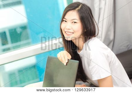 Young Asian Woman Using Laptop On Bed At Condominium