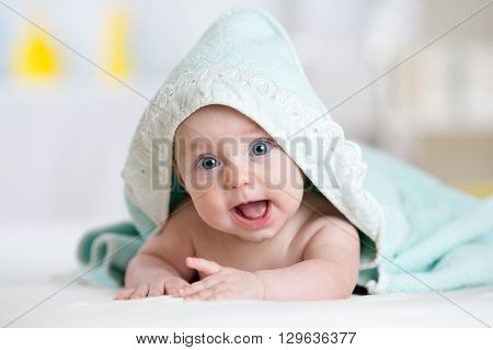 happy baby infant in towel after bathing in living room