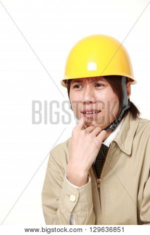young Japanese construction worker worries about something