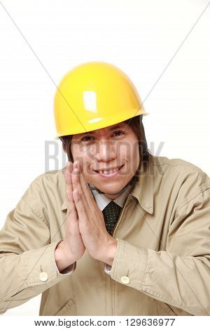 portrait of construction worker folding his hands in prayer on white background