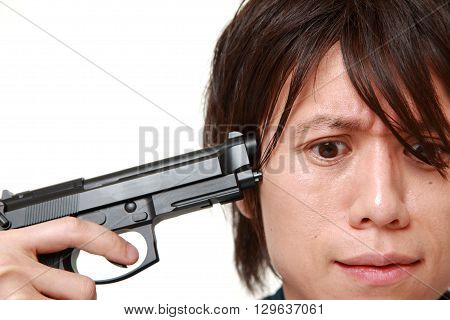 portrait of Japanese man going to shoot himself on white background