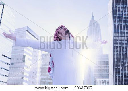 Arabian person standing in the city while wearing a headscarf with outstretched hands and enjoy freedom