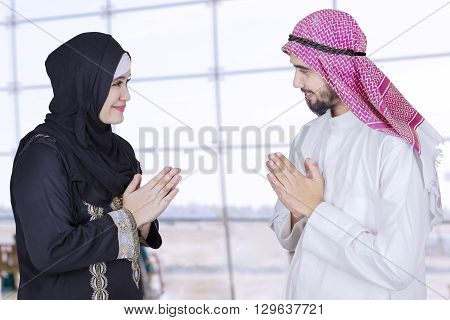 Portrait of two Arabic businesspeople meet in the airport and give a greeting with hands gesture