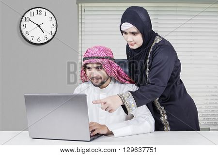 Portrait of Arabian couple working together with laptop in the office