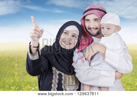 Portrait of happy middle eastern family standing on the meadow while looking at something on the sky