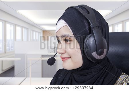 Portrait of beautiful Arabic helpline operator using headset to work in the office room