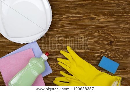 Detergent, sponge, dishes, rags and latex gloves on wooden background